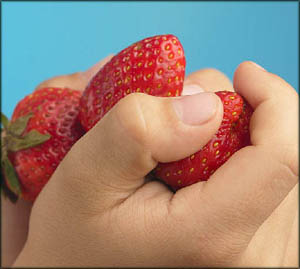 Helping out in the kitchen. Child hands holding strawberries.