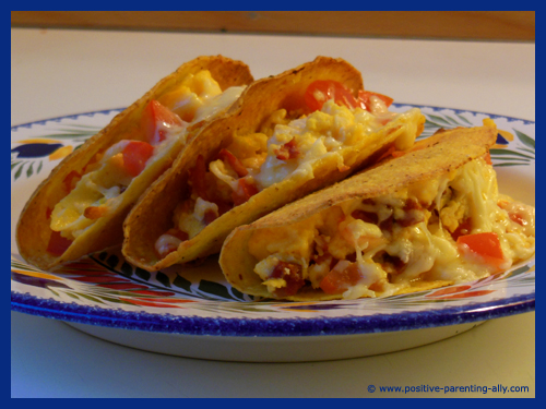 Beautiful brainy breakfast tacos with eggs, tomatos, cheese and chorizo.