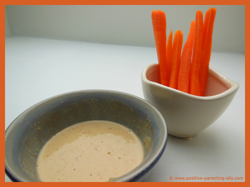 Thin carrot sticks with peanut butter dip as healthy foods for kids.