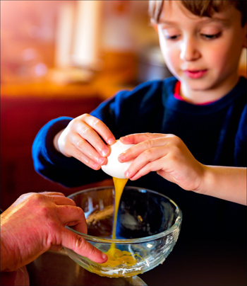 Child baking and breaking an egg.