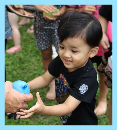 Little boy being given a blue water balloon.
