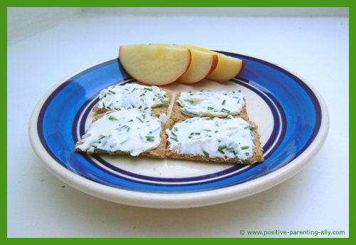 Crackers with creme cheese mixed with chive as a healthy quick snack for kids.