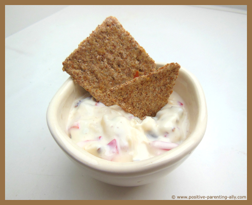 Delicious kids snack: whole grain cracker with cream cheese dip.