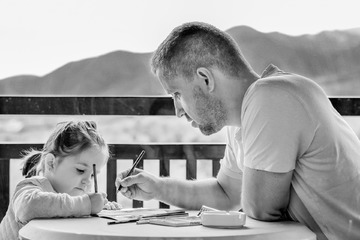 Father and daughter drawing or doing homework.