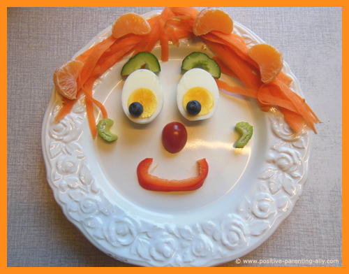 Funny face of vegetables and fruit on a plate as fun snacks for kids.Egg eyes, carrot hair, celery ears and bell pepper mouth. Great as raw snacks for toddlers.