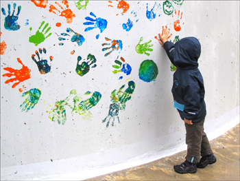 Colorful handprints in paint on white wall.