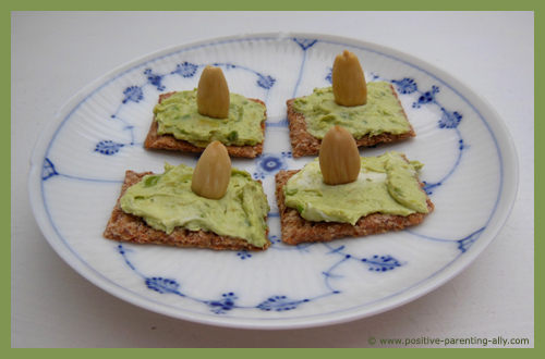 Avocado spread on cracker as healthy snacks for kids.