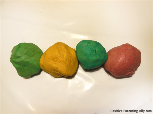 Homemade play doh in red, green, blue and yellow colors.
