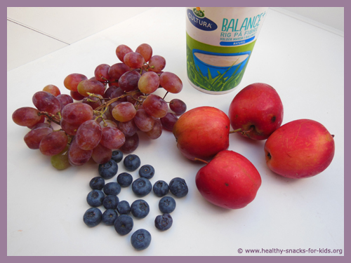 Ingredients for fruit smoothie: grapes, blueberries, apples and yoghurt.
