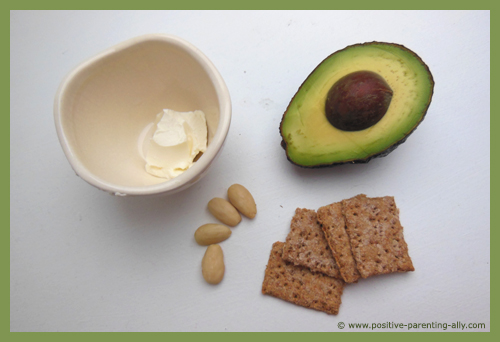 Ingredients for avocado spread on whole grain crackers.