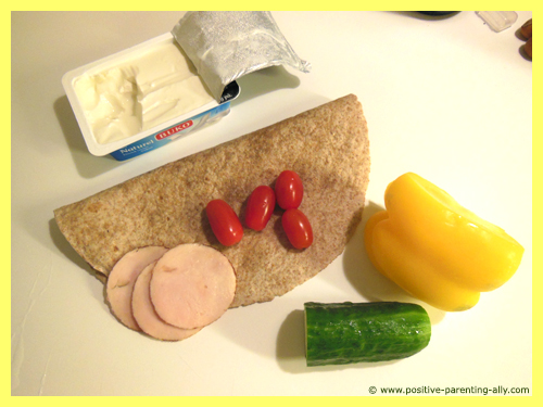 Tortilla snack ingredients: cream cheese, tomatoes, chicken, bell pepper and cucumber.