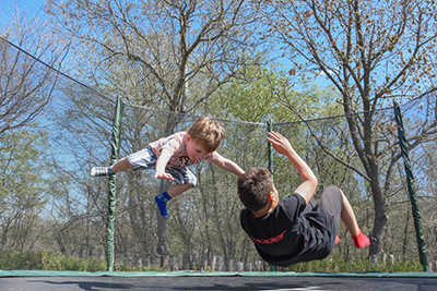 Children jumping on a trampoline.