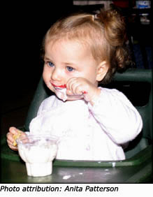 Little toddler girl eating with a spoon.