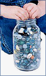 Toddler milestones of making things fit: Toddler hands making marbles fit into a jar.