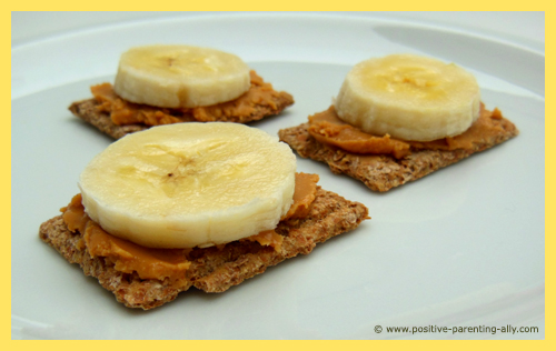 Quick easy snacks for kids with crackers, peanut butter and banana slices.