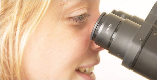 Girl looking through microscope: Great kids science websites on biology.
