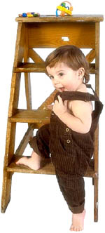 Little toddler girl about to climb small wooden ladder.