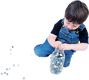 Tidying games: Boy picking up his marbles.