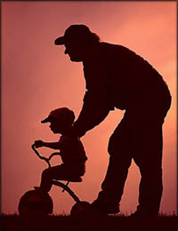 Silhoutte of father pushing little boy on his tricycle.