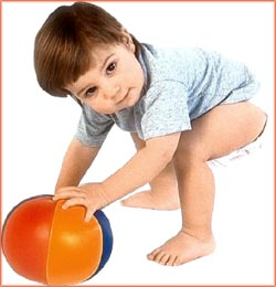 Toddler reaching down for soft ball.