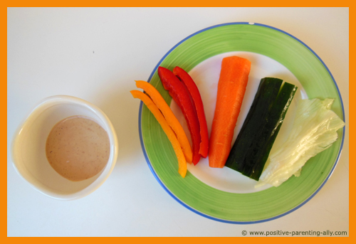 The colorful vegetable rainbow for kids with peanut butter dip. Easy snack recipe for toddlers.