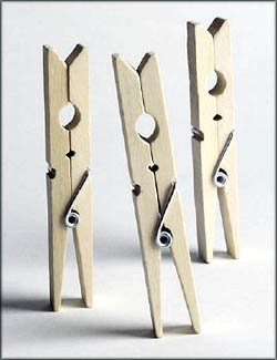 Playing with clothes pegs. Three clothes pegs stading in upright position.