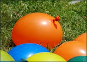 Fun activities for toddlers: Throwing water balloons. Orange water balloon in the grass.