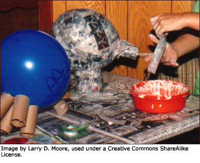 Kids making fun crafts for kids in terms of paper mache on balloons.
