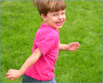 Little boy running on grass in the game of Mother Hen and the Colored Eggs.