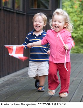 Danish kids running freely with Danish flag in their hands.