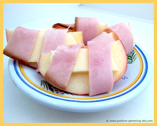 Easy snacks for kids to make in no time: apple and cheese rolled with ham.