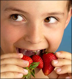 Healthy eating for kids: boy about to eat strawberries