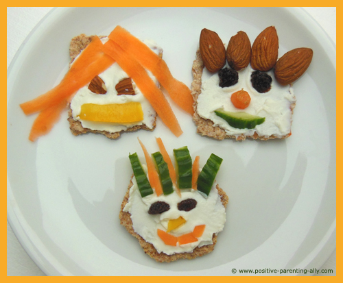 Funny kids snacks: funny faces on crackers with carrot, cucumber, raisins, almonds and cream cheese