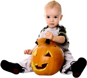 Cute little toddler sitting with a big pumpkin head for Halloween.