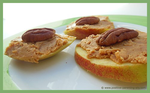 Healthy recipes for kids with apple slices, peanut butter and pecan nuts.