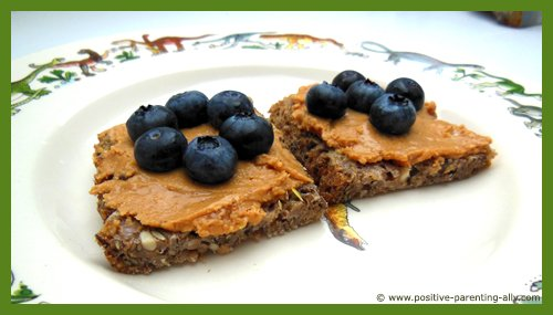 Quick easy snack for kids: peanut butter on whole grain bread topped with blueberries.