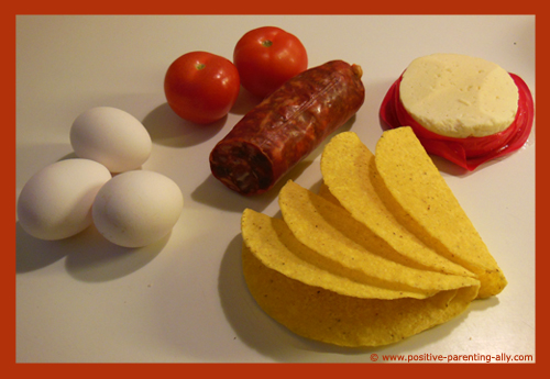 Ingredients for the breakfast taco: Eggs, tomatos, chorizo sausage, cheese and taco shells.
