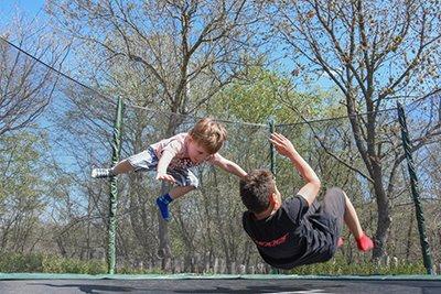 Children jumping on a trampoline.