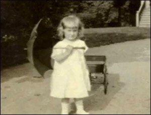 Old photo of Mary Ainsworth as little girl holding an umbrella.