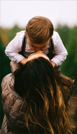 Child and mother bonding with heads close together.