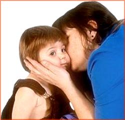 Toddler kissed by mother.