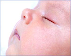 Newborn  sleeping patterns: Sleeping infant in profile, close-up.