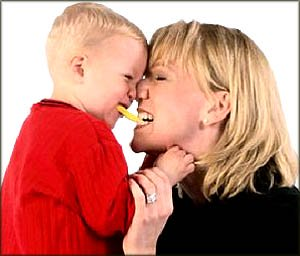 Fun toddler games: Mom and son intimate moment: rubbing noses, biting the same bisquit.