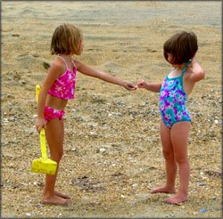 Reaching the milestone of cooperative playing: Two girl playing together on the beach.