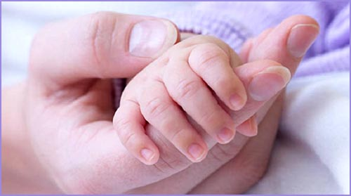 Baby hand holding mom's finger. Picture of hands.