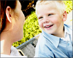 Happy blond boy talking to his mother.