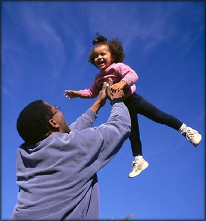 Parenting style test: Father throwing his little girl up into the air.