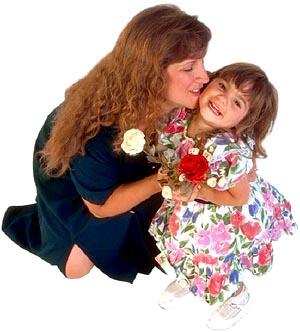 Mother kneeling hugging her little girl.
