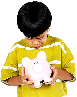 Boy looking into his piggy bank for money.