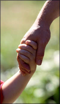 Stages of child development: boy holding his father's hand.